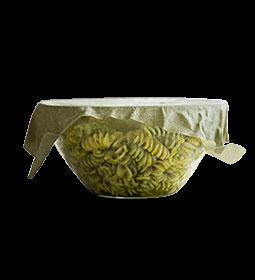 Ein grün-weiß gemustertes Tuch aus Bienenwachs, das eine Glasschale mit Pesto-Nudeln abdeckt